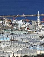 東京電力福島第1原発の敷地内に林立する、汚染水を浄化した後の処理水などを保管するタンク。奥左から1、2、3号機=1月