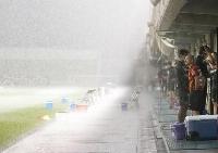 名古屋―岡山戦が雷雨で中断し、ピッチの様子を見る名古屋の吉田豊(手前)ら。後半を開始できず前半終了時点で中止となった=名古屋市港サッカー場