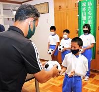 神田社長(手前)からサッカーボールを受け取る児童