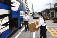 JRバスの荷台の様子を見る「小諸駅のまど」代表の金山裕美さん(右)=小諸駅前