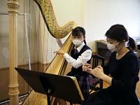 小諸高校音楽科の講師に就任した井田さん(右)からハープのレッスンを受ける岩下さん