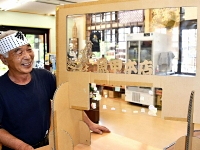 店名と佐久鯉をあしらった「タクシールド」を示す、川魚販売店の市川章人(あきと)社長