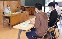 学生や生徒に戦争体験を語る清水さん(左)