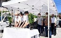 災害伝承之碑前の献花台に花を供える参加者