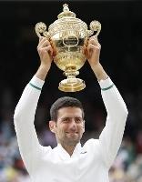 男子シングルスで優勝し、トロフィーを掲げるノバク・ジョコビッチ=ウィンブルドン(ロイター=共同)