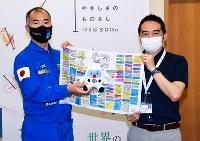 ご当地キャラクター「フックン船長」のぬいぐるみを返す野口聡一さん(左)=20日午後、茨城県つくば市役所