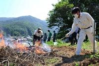 ソバを栽培する畑に火入れをする山根さん(右)ら