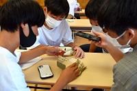 清水さんが保管してきた軍隊手帳と階級章を見る高校生