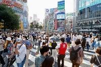 東京・渋谷のスクランブル交差点を行き来するマスク姿の人たち=23日午後