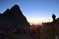 北アルプス槍ケ岳越しに御来光を眺める登山者ら=23日午前4時51分、槍ケ岳山荘近く