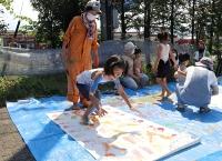 体に絵の具を塗って紙に色を付ける小学生