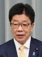 記者会見する加藤官房長官=26日午前、首相官邸