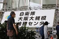 新型コロナウイルスワクチン大規模接種センター大阪会場に入る人たち=6月、大阪市