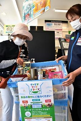 回収箱の食品を受け取る大沢さん(左)