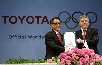 2015年3月、IOCの最高位のスポンサー制度「TOPプログラム」の契約締結を発表するIOCのバッハ会長(右)とトヨタ自動車の豊田章男社長=東京(AP=共同)