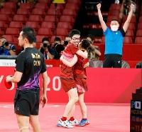 混合ダブルス決勝で中国組を破って優勝し、抱き合って喜ぶ水谷隼(中央左)、伊藤美誠組。右奥は田勢邦史コーチ=東京体育館
