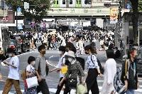 東京・渋谷のスクランブル交差点をマスク姿で歩く人たち=6月11日