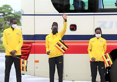 選手村へ向かうバスの前で、集まった人に手を振るウガンダの選手