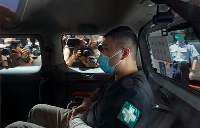 警察車両で香港の裁判所に到着した被告の男性=2020年7月(AP=共同)