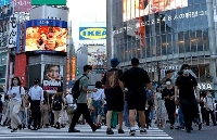 東京・渋谷のスクランブル交差点を歩く大勢の人たち。電光掲示板(右上)は過去最多となった東京都の新型コロナ感染者数を表示していた=27日午後