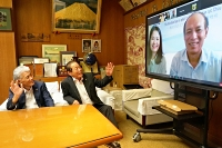 モニター画面に映し出されたバン代表(右端)とオンラインで懇談する(左から)渡辺議長、由井村長=27日、川上村役場