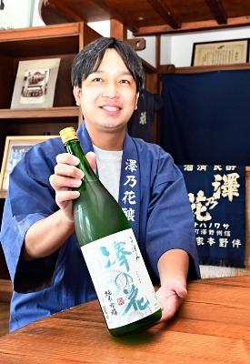 上位2銘柄の一つに選ばれた純米吟醸酒を手に笑顔を見せる伴野さん