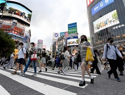 東京・渋谷のスクランブル交差点を歩くマスク姿の人たち。国内で新たに確認された新型コロナウイルス感染者が初めて1万人を超えた=29日午後