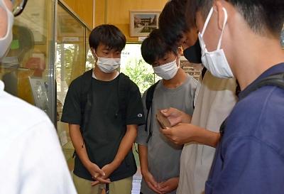 旧上田飛行場周辺に落とされた爆弾の破片を見る上田染谷丘高の生徒ら