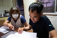 支援本格化前の試行オンライン学習でテキストを読む元技能実習生のベトナム人(右)と手伝う農家=7月26日、川上村