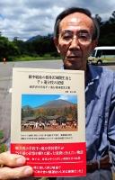 軽井沢町にあった「千ケ滝分校」の跡地で、文集を手にする倉石さん。表紙の写真は映画「カルメン故郷に帰る」に登場した分校