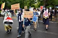 政府提出の入管難民法改正案の廃案を求めデモ行進する参加者=5月16日、東京・日比谷公園前