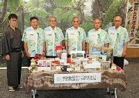 ふるさと納税制度を活用した資金調達を始めた鹿児島県奄美市の朝山毅市長(左から4人目)ら=13日午後、奄美市役所