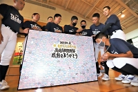 市民のメッセージを貼り付けたボードを見る高遠高校野球部員