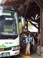 激しく雨が降る中、下山用のバスに乗り込む宿泊客ら=14日午前9時53分、松本市安曇