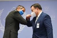 19日、あいさつを交わす梶山経産相(右)とIAEAのグロッシ事務局長=ウィーン(共同)