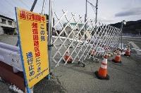 福島県浪江町津島地区に設置されている帰還困難区域を示す看板とバリケード=1月