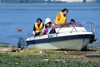 舟の上からペットボトルなどのごみを回収する高校生ら