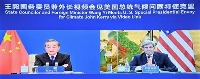 ビデオ通話で会談する中国の王毅国務委員兼外相(左)と米国のケリー大統領特使=1日(新華社=共同)