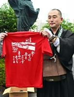 播隆上人のイラストをあしらったチャリティーTシャツを紹介する荻須代表