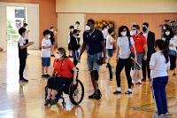 シェルマン選手(前から2人目)、メリッサ選手(3人目)らを拍手で迎える松川中央小の児童