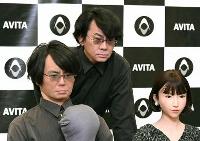 記者会見で開発したロボットと並んで撮影に応じる石黒浩大阪大教授(中央)=7日午後、東京都渋谷区