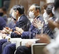 東京五輪の各国選手団の入場行進で拍手する菅首相=7月23日、国立競技場