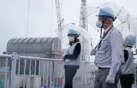 東京電力福島第1原発を視察するIAEAのエブラール事務次長(左)=8日(東電提供)