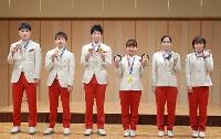 日本卓球協会の東京五輪報告会で、メダルを手にポーズをとる(左から)張本智和、丹羽孝希、水谷隼、伊藤美誠、石川佳純、平野美宇=12日、東京都内