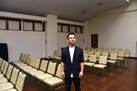 公演を予定した飯田市内の会場で「来年必ず実現したい」と話す小林さん