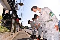 母子3人が亡くなった住宅の前で頭を下げる今井市長(手前)ら=15日午後2時30分、岡谷市川岸東