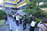 3連休中日の19日は晴れて気温が上昇し、行楽地には県内外の観光客が訪れた。国宝松本城では天守への入場待ち時間が最大70分となり、長い列ができた=19日午後2時4分、松本市