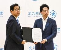 北九州市役所を訪問し、北橋健治市長(左)に要請文を手渡した小泉環境相=22日午後