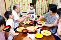 照利さんの遺影を囲んで夕食を食べる長山さん一家(右から2人目が文枝さん)=17日夜、愛知県豊田市
