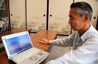 噴火1分前に撮影された八丁ダルミの様子をパソコンで見る中西さん=14日、石川県小松市